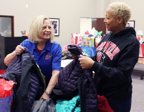 Text Box: Ms. Phillips (right) and Board President Carla Fahey organize coats for distribution to students.